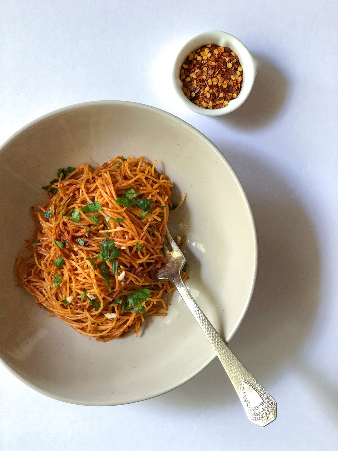 Pasta in a white round dish with a fork Caramelized Shallot Pasta Recipe