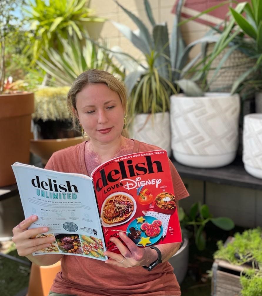 girl with blonde hair with orange shirt holding a red cover magazine in front of green plants