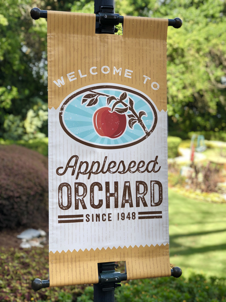 Brown, Red and White sign with an apple on it that says Appleseed Orchard