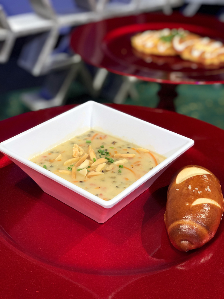 White square bowl with ham soup and a pretzel roll on a red plate