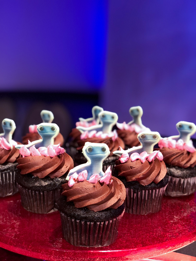 Brown chocolate cupcakes with a lizard topper on a red plate