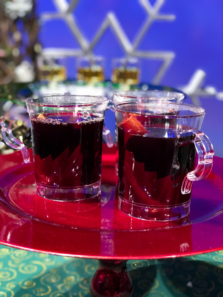 Clear plastic cups with red wine on a red plate