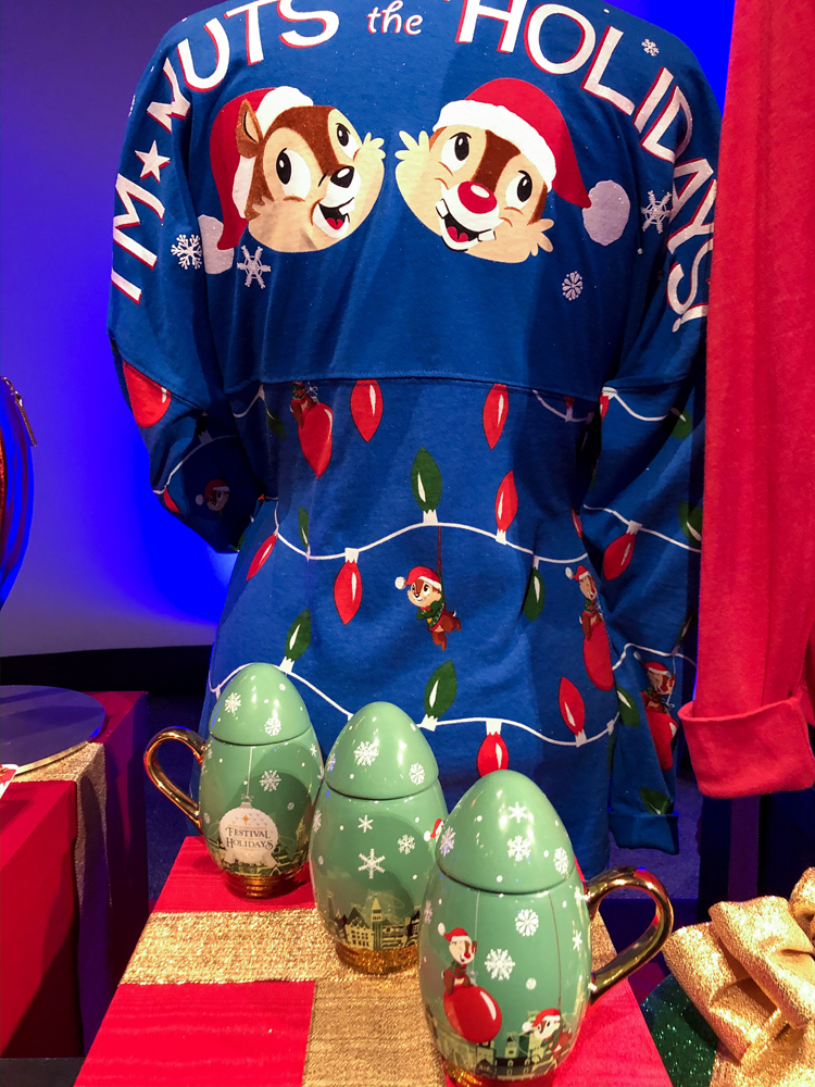 Blue long sleeved top with two chipmunks with Santa hats on and a green mug on a table