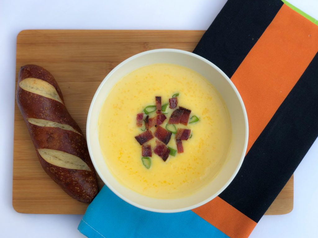 White bowl of cheese soup on a brown board with brown bread and orange and blue kitchen towel