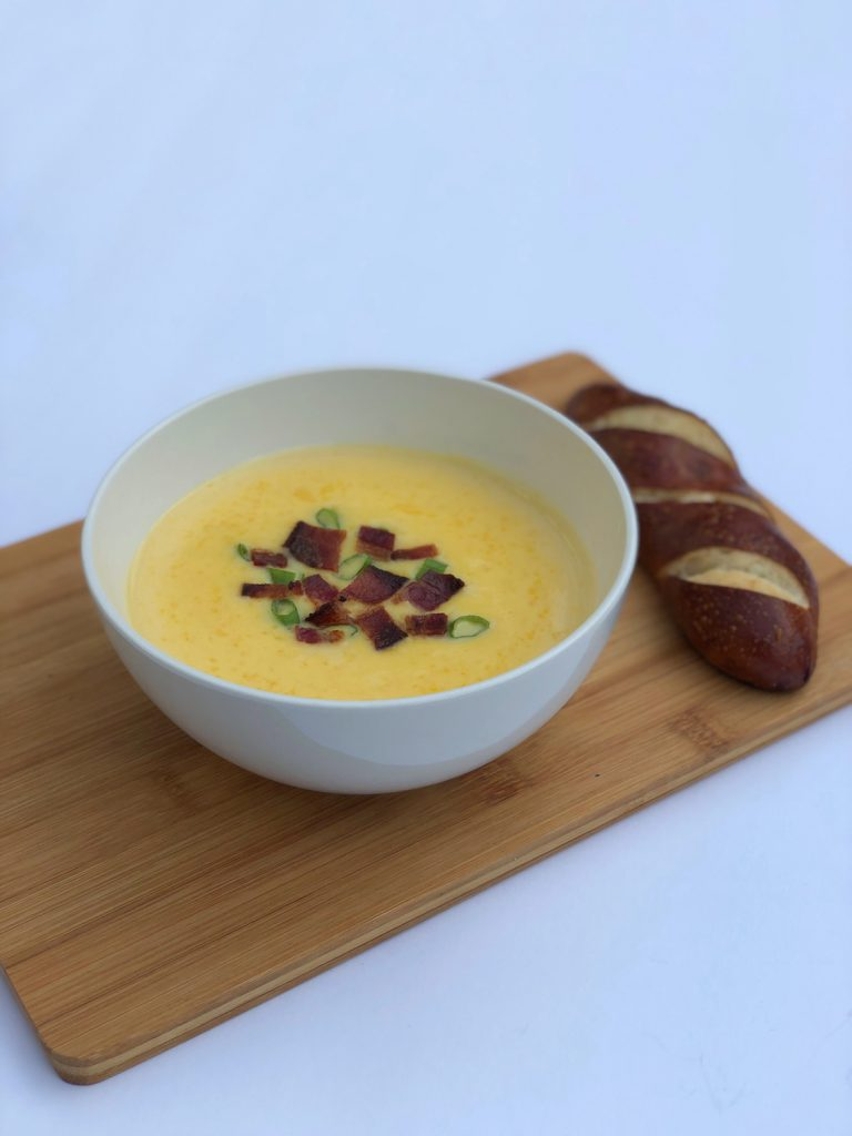 White bowl of cheddar cheese soup on a brown board with brown bread on a white background