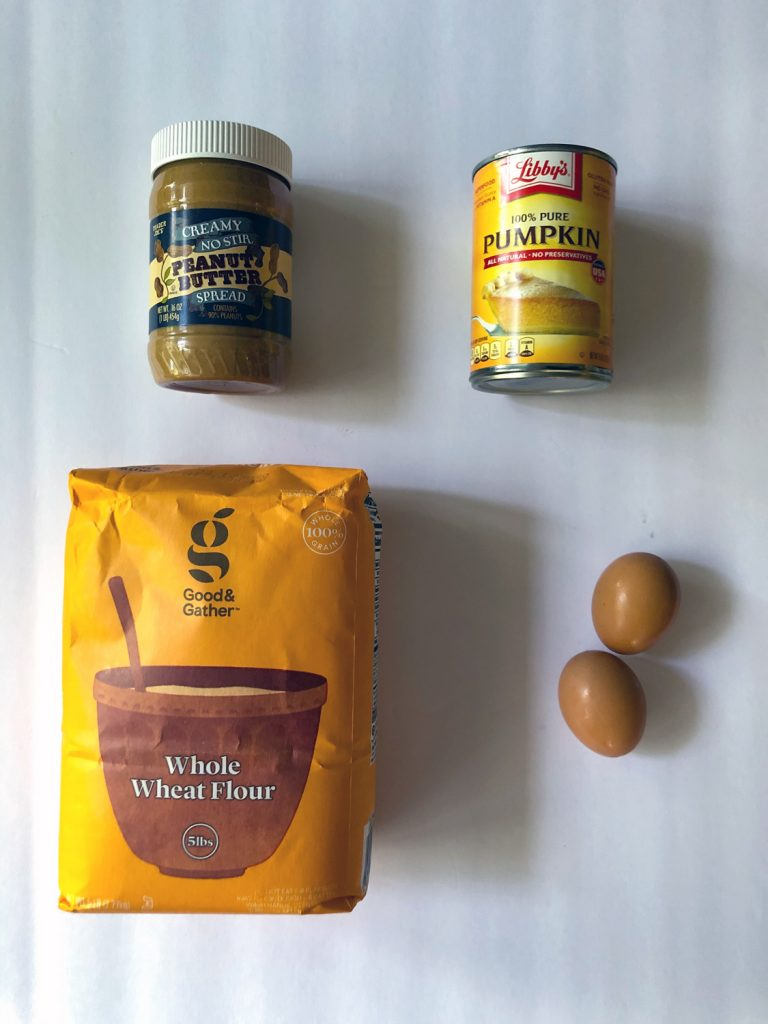 Jar of peanut butter, can of pumpkin puree, orange bag of whole wheat flour and two brown eggs on a white background.