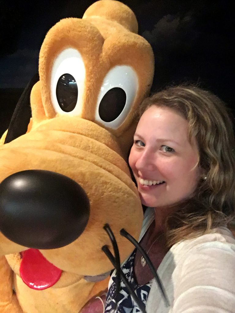 Yellow Disney World Pluto Dog with a blonde haired girl.