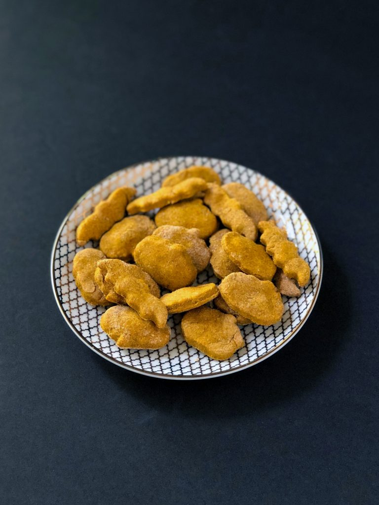 Peanut Butter Pumpkin Dog Treats on a white and gold plate on a black background