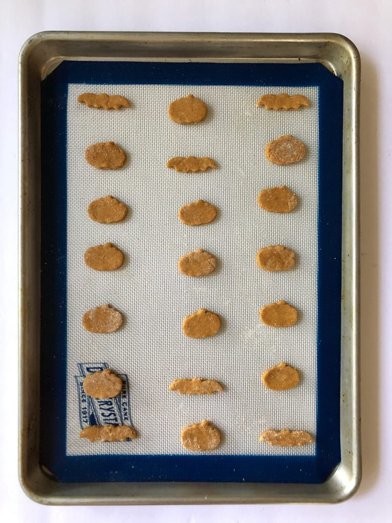 Peanut Butter Pumpkin Dog Treats on a white and blue silicone mat and stainless steel tray